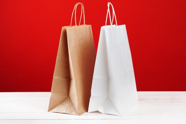 Papiereinkaufstaschen mit kopienraum auf rotem hintergrund Premium Fotos