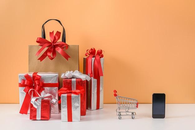 Papiereinkaufstaschen und warenkorb oder laufkatze, viel geschenkbox, smartphone auf weißer tabelle und orange pastellwand Premium Fotos