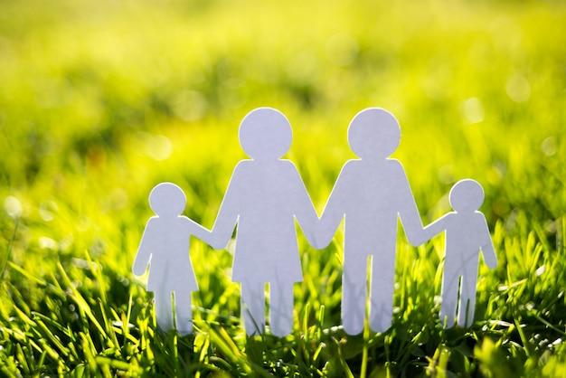Papierfamilie auf hintergrund des grünen grases Premium Fotos