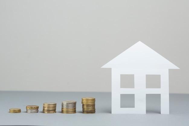 Papierhausmodell mit stapel zunehmenden münzen auf grauer oberfläche Kostenlose Fotos
