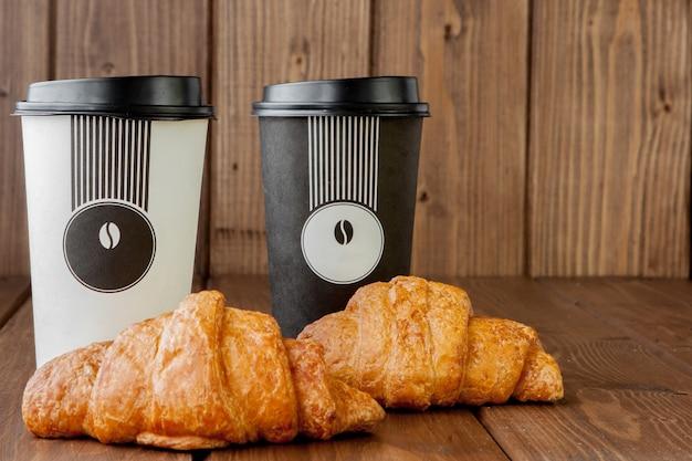 Papierkaffeetasse und croissants auf hölzernem hintergrund, kopierraum. Premium Fotos