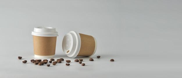 Papierkaffeetasse und kaffeebohnen auf weißem hintergrund. Premium Fotos