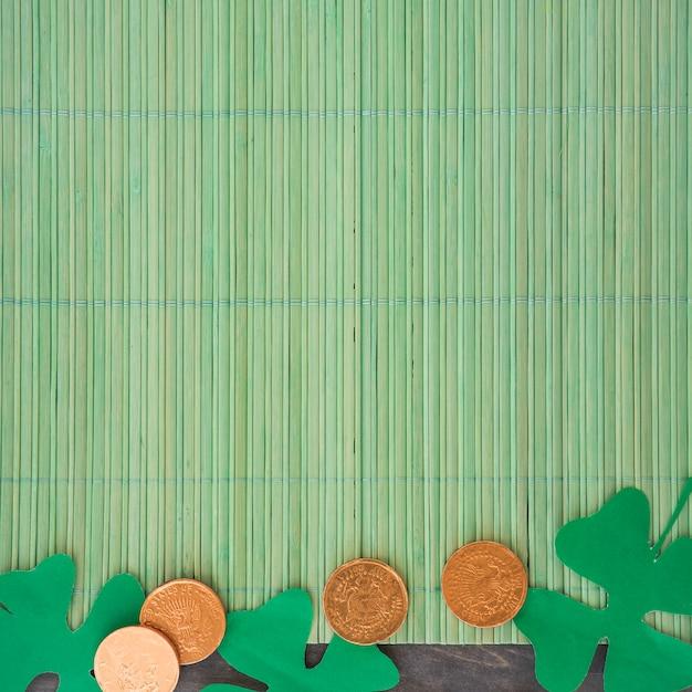 Papierklee nahe münzen auf bambusmatte Kostenlose Fotos