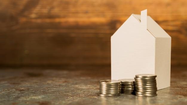 Papierminiaturhaus mit stapel münzen auf boden gegen hölzernen hintergrund Kostenlose Fotos