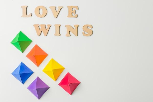 Papierorigami in lgbt-farben und liebe gewinnt worte Kostenlose Fotos