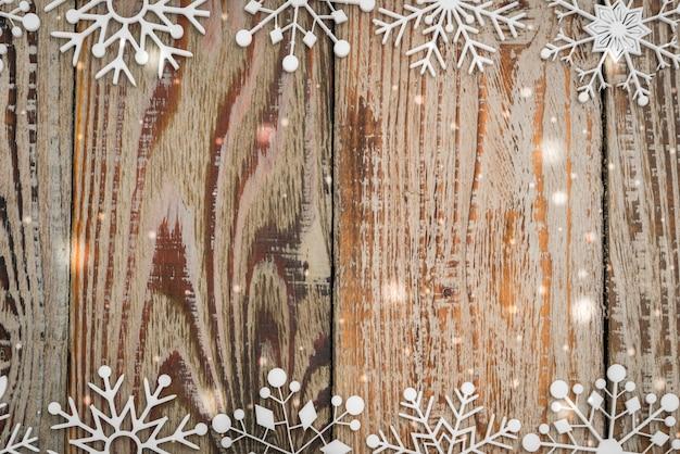 Papierschneeflocken auf hölzernem hintergrund Kostenlose Fotos