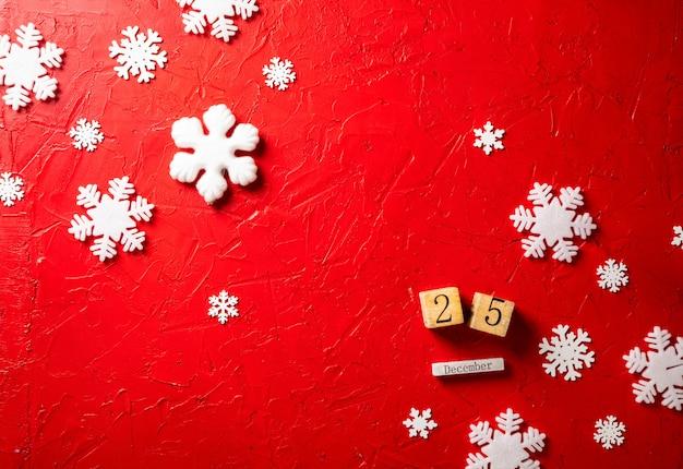 Papierschneeflocken und hölzerner kalender auf rotem hintergrund Premium Fotos