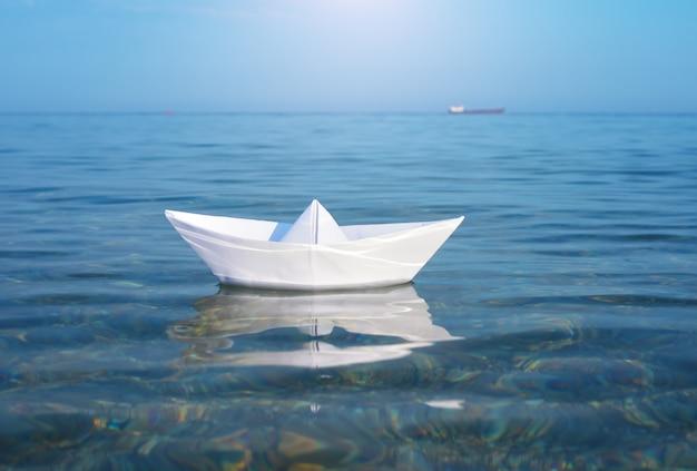 Papierspielzeugschiff und tiefes blaues meer. Premium Fotos