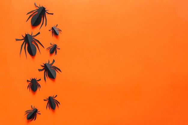 Papierspinnen auf einem orangefarbenen hintergrund Premium Fotos