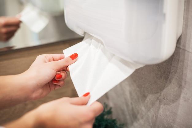 Papiertuchspender. hand der frau nimmt papiertuch im badezimmer. Premium Fotos