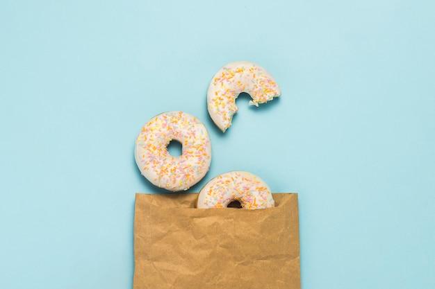 Papiertüte und frische leckere süße donuts auf blauem grund. konzept von fast food, bäckerei, frühstück, süßigkeiten. minimalismus. flache lage, draufsicht. Premium Fotos