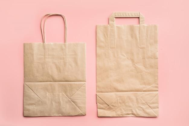 Papiertüten für das einkaufen des nullabfalls auf rosa. Premium Fotos