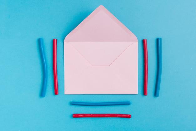 Papierumschlag und buntes lakritz um ihn herum Premium Fotos