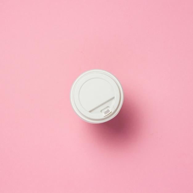 Pappbecher mit einem plastikdeckel, kaffee oder tee, auf einem rosa hintergrund. fast-food-konzept, bäckerei, frühstück, süßigkeiten, café, essen zum mitnehmen. speicherplatz kopieren. flache lage, draufsicht. Premium Fotos