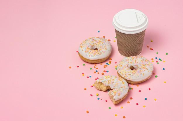 Pappbecher mit kaffee oder tee, frische leckere süße donuts auf einem rosa hintergrund. fast-food-konzept, bäckerei, frühstück, süßigkeiten, café. speicherplatz kopieren. Premium Fotos