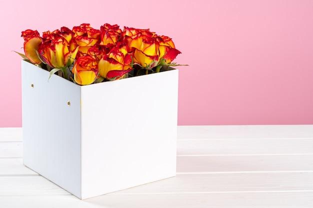 Pappschachtel mit rosen auf rosa hintergrund Premium Fotos