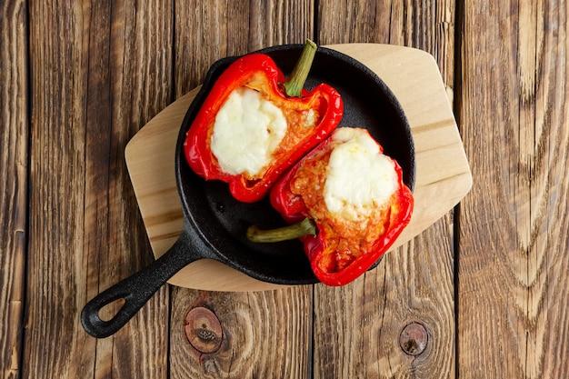 Paprika gefüllt mit fleisch mit geschmolzenem käse mozzarella oben im ofen in gusseisen skille gebacken Premium Fotos