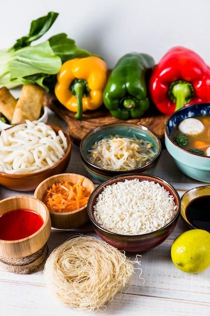 Paprika; sprießen bohnen; reis; udon-nudeln; saucen und trockene reissuppennudeln auf weißem schreibtisch Kostenlose Fotos