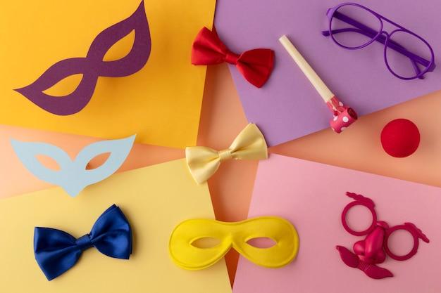 Parade-maske und zubehör auf verschiedenfarbigen papieren Premium Fotos