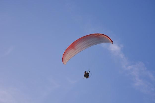Paramotor (angetriebener gleitschirm) mit dem rot-weißen fallschirm, der in himmel, extremer sport fliegt. Premium Fotos