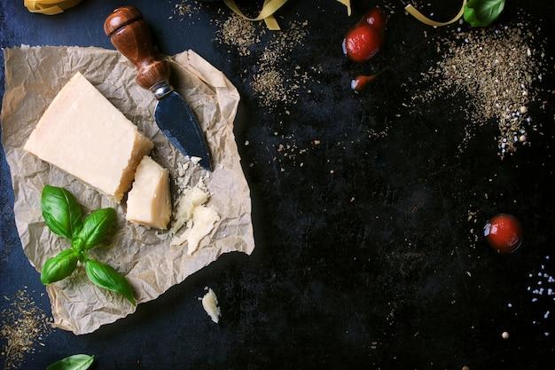 Parmesan pasta-rezept mit einem stück käse und rohen nudeln und anderen zutaten Kostenlose Fotos