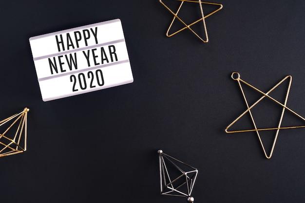 Partei-leuchtkasten des guten rutsch ins neue jahr 2020 mit draufsicht des sterndekorations-einzelteils über schwarze hintergrundtabelle Premium Fotos