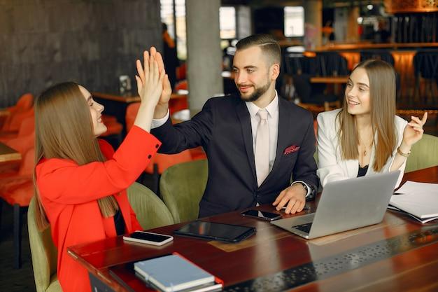 Partner, die am tisch sitzen und in einem café arbeiten Kostenlose Fotos