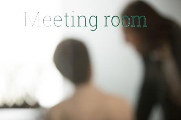 Partner, die hinter geschlossener glastür des konferenzraums verhandeln Kostenlose Fotos