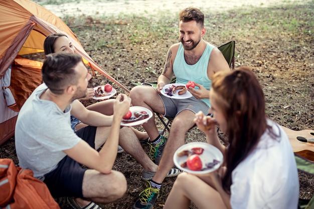 Party, camping der männer- und frauengruppe am wald. entspannen und grillen gegen grünes gras essen. urlaub, sommer, abenteuer, lifestyle, picknick-konzept Kostenlose Fotos