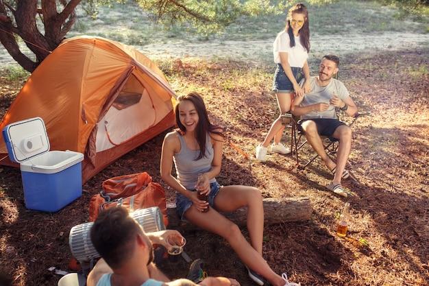 Party, camping der männer- und frauengruppe am wald. sie entspannen sich gegen grünes gras. der urlaub, sommer, abenteuer, lifestyle, picknick-konzept Kostenlose Fotos