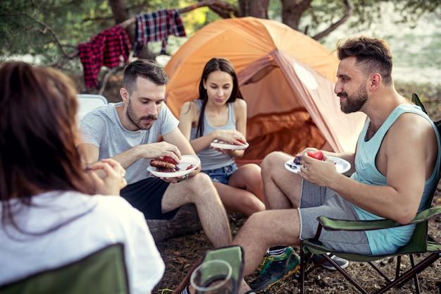 Party, camping der männer- und frauengruppe am wald. sie entspannen sich und essen grillen Kostenlose Fotos