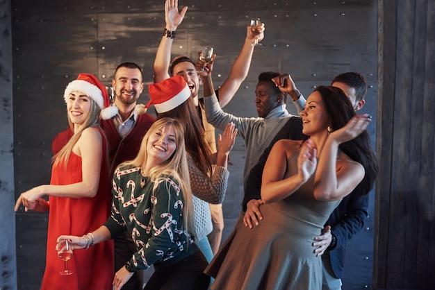 Party mit freunden. sie lieben weihnachten. gruppe nette junge leute, welche die wunderkerzen und sektkelche tanzen in partei des neuen jahres und schauen glücklich tragen. konzepte zum zusammenleben Premium Fotos