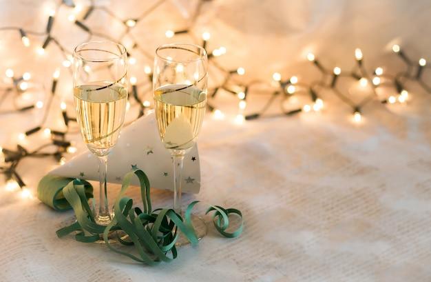 Partyelemente und -gläser des neuen jahres mit champagnerkarte mit dem platz zum schreiben Premium Fotos