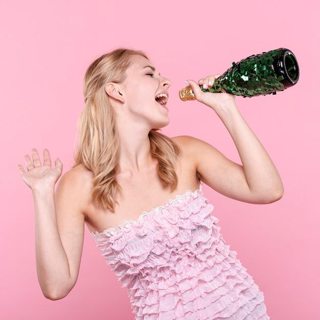 Partyfrau, die an der sektflasche singt Kostenlose Fotos