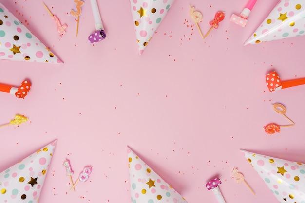 Partyhut und kerzen, die auf rosa hintergrund liegen. Premium Fotos