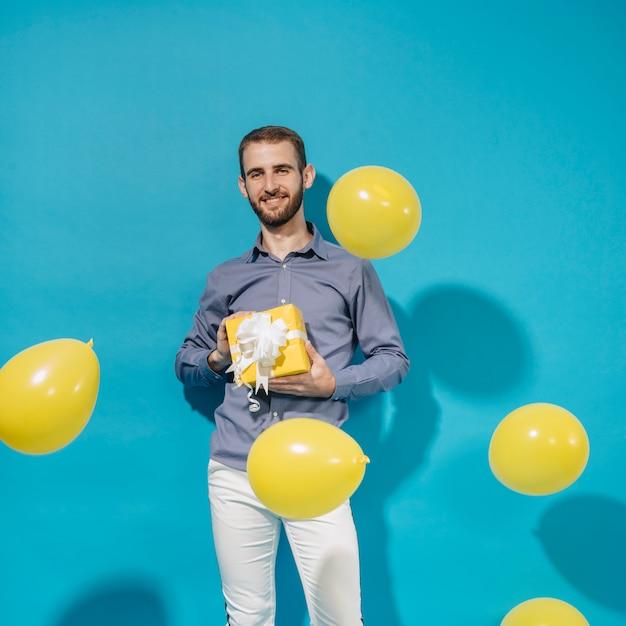 Partyjunge, der mit geschenk und ballonen aufwirft Kostenlose Fotos