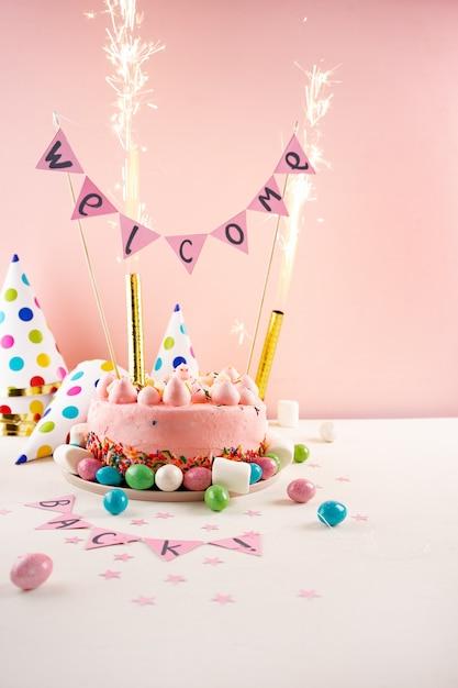Partykuchen mit farbe besprüht und wunderkerzen. willkommen zurück konzept Premium Fotos