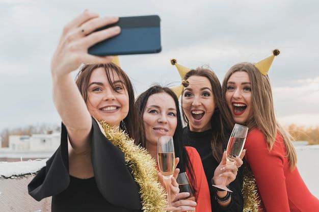 Partymädchen, die gruppen-selfie auf der dachspitze nehmen Kostenlose Fotos