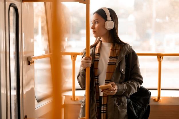 Passagier, der musik in der straßenbahn hört Kostenlose Fotos