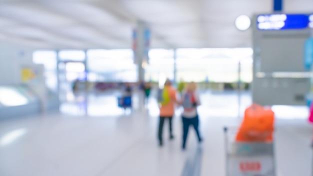 Passagiere am flughafenabfertigungsgebäude verwischten hintergrund Premium Fotos