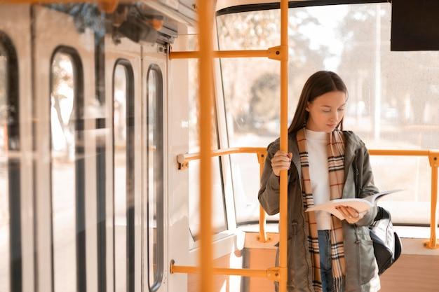 Passagierin, die mit der straßenbahn liest und fährt Kostenlose Fotos