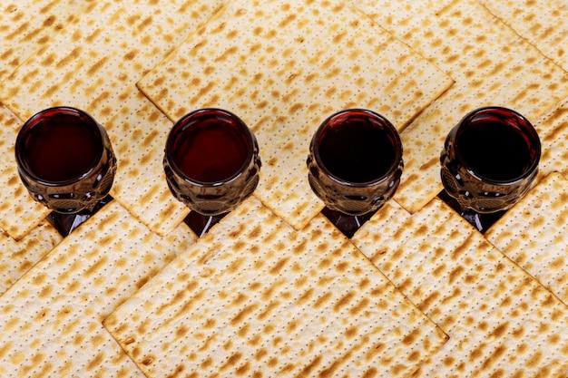 Passah hintergrund. wein und matzoh jüdisches feiertagsbrot über holzbrett. Premium Fotos