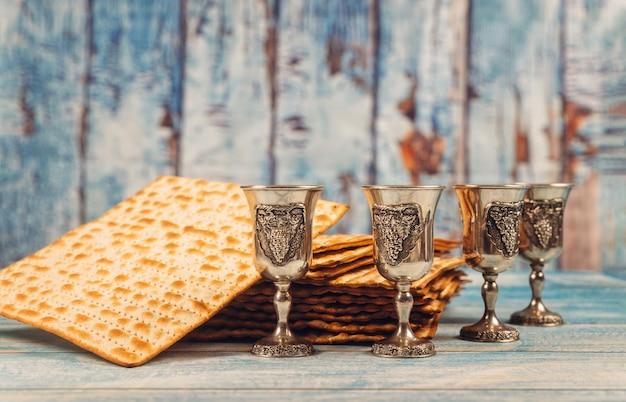 Passahfest vier gläser wein und jüdisches feiertagsbrot des matzoh über hölzernem brett. Premium Fotos