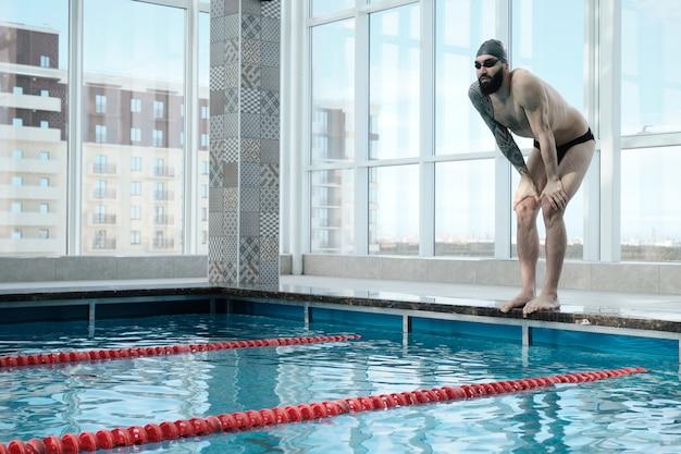 Passen sie bärtigen mann in schwimmbrille und mütze, die am rand des pools stehen und sich auf das schwimmen vorbereiten Premium Fotos