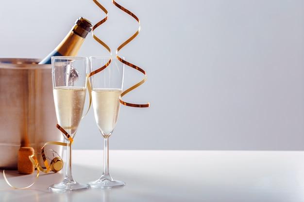 Passen sie glas champagner mit flasche im metallbehälter zusammen. neujahr feierlichkeiten Premium Fotos