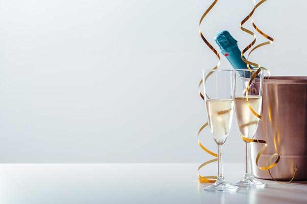 Passen sie glas champagner mit flasche im metallbehälter zusammen Premium Fotos
