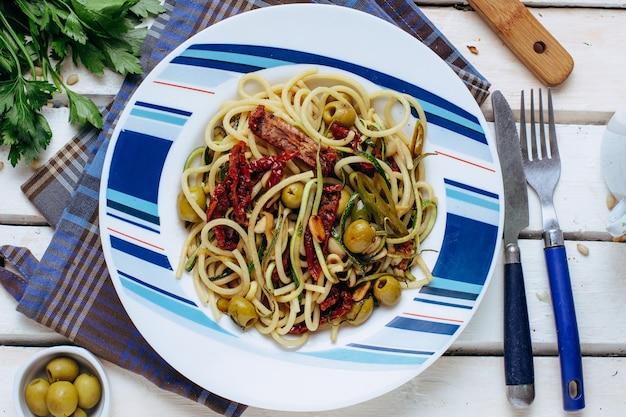 Pasta alla puttanesca mit knoblauch, oliven, kapern, tomaten Premium Fotos