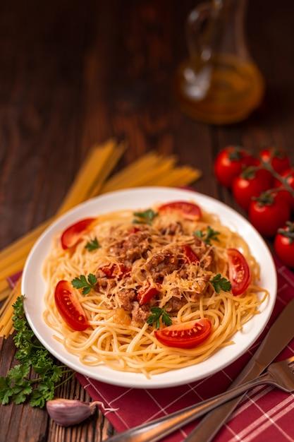 Pasta bolognese mit tomatensauce und hackfleisch, geriebenem parmesan und frischer petersilie - hausgemachte gesunde italienische pasta Premium Fotos