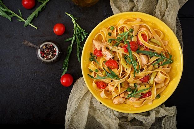 Pasta fettuccine mit tomaten, zucchini und hähnchenfilet in schüssel. flach liegen. ansicht von oben Premium Fotos