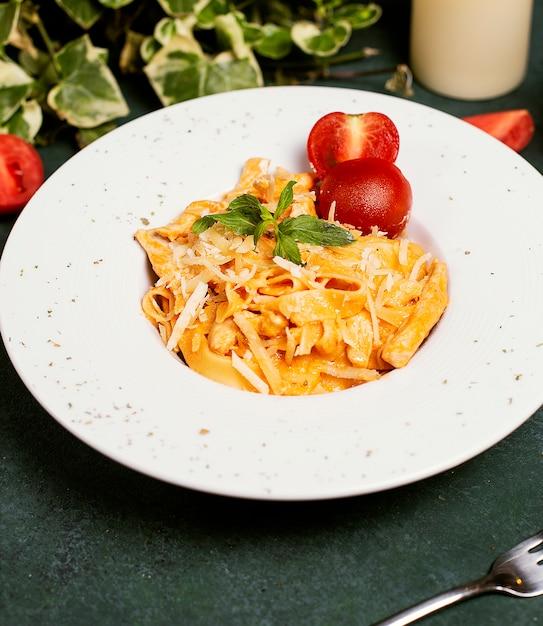 Pasta in tomatensauce mit gehacktem parmesan, tomaten und basilikum. Kostenlose Fotos